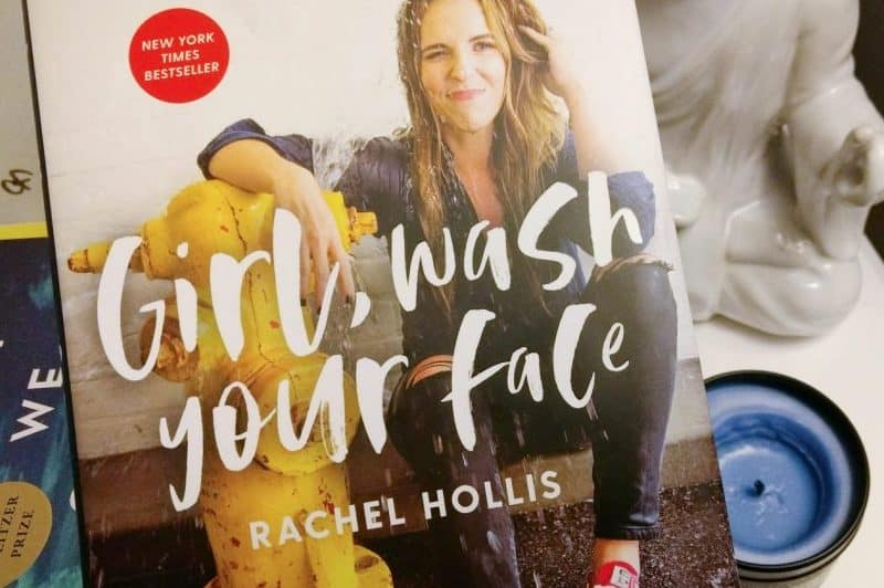 A photograph of the book cover of Girl Wash Your Face, a candle and home decor