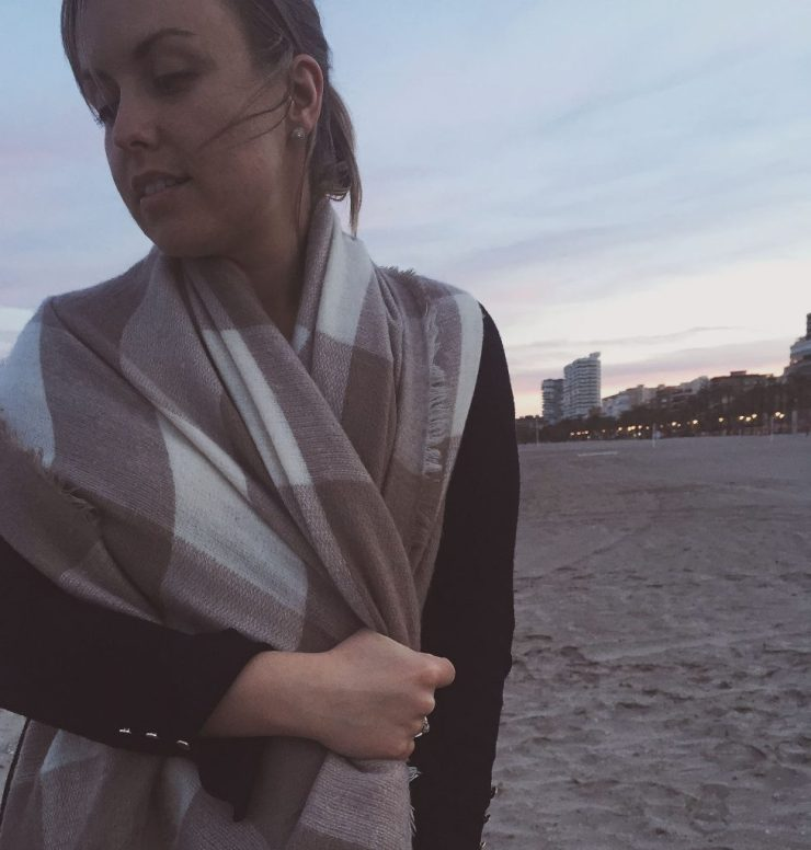 cozy in a scarf on playa san juan at dusk