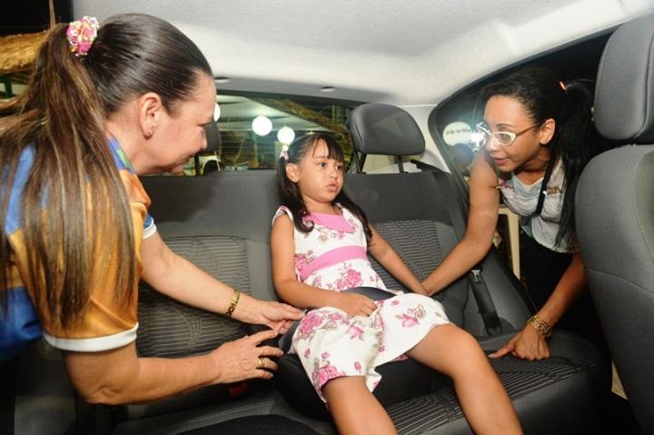 Educadora do trânsito do DETRAN explica uso da cadeirinha para mãe durante ação educativa no stand do departamento na Lagoa da Jansen