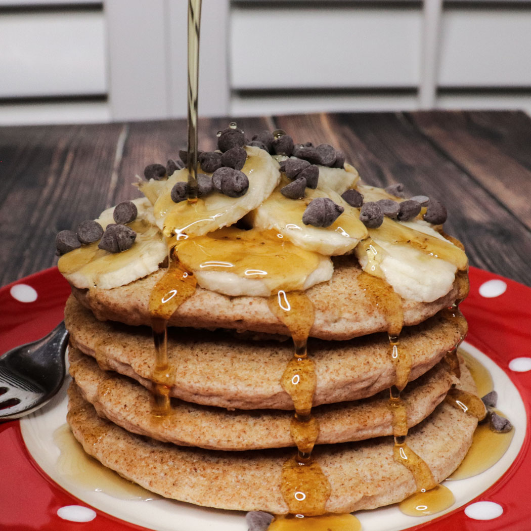 fluffy whole wheat vegan pancakes with maple syrup and chocolate chips on the plate