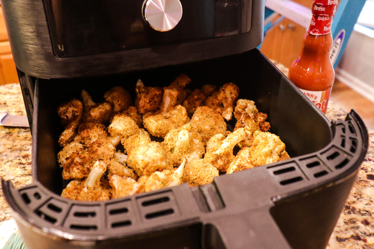 Crispy air fried cauliflower coming out of air fryer