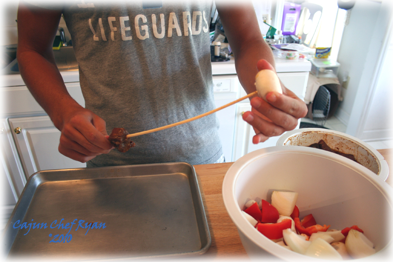 Ben threading the ingredients on the skewers for kabobs