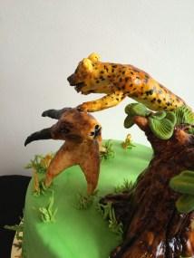 A cheetah attacking a antelope cake.