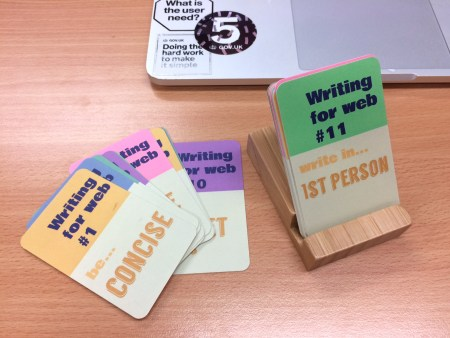 Web tip cards, bamboo stand and laptop showing stickers saying 5, What is the user need and Doing the hard work to make it simple. Card text shows: Writing for web tip 1 be concise and tip 11 Write in first person.