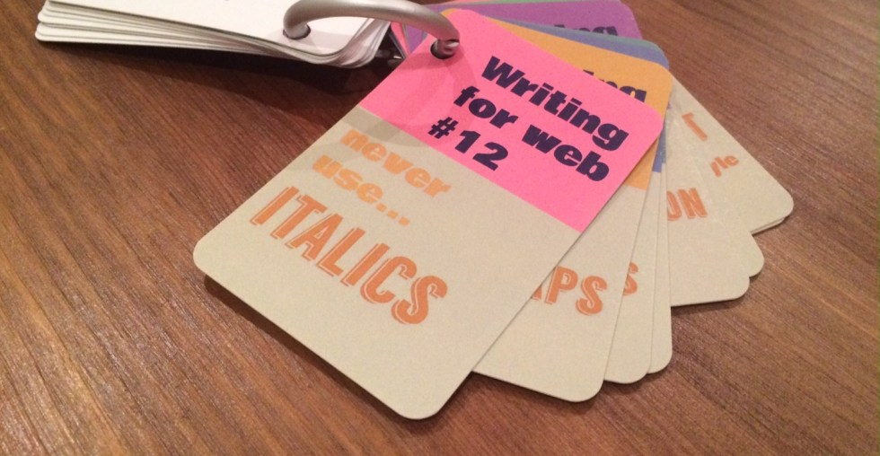 Writing for web tip cards on a keyring on a wooden desk. Text showing says: Writing for web #12 never use italics.