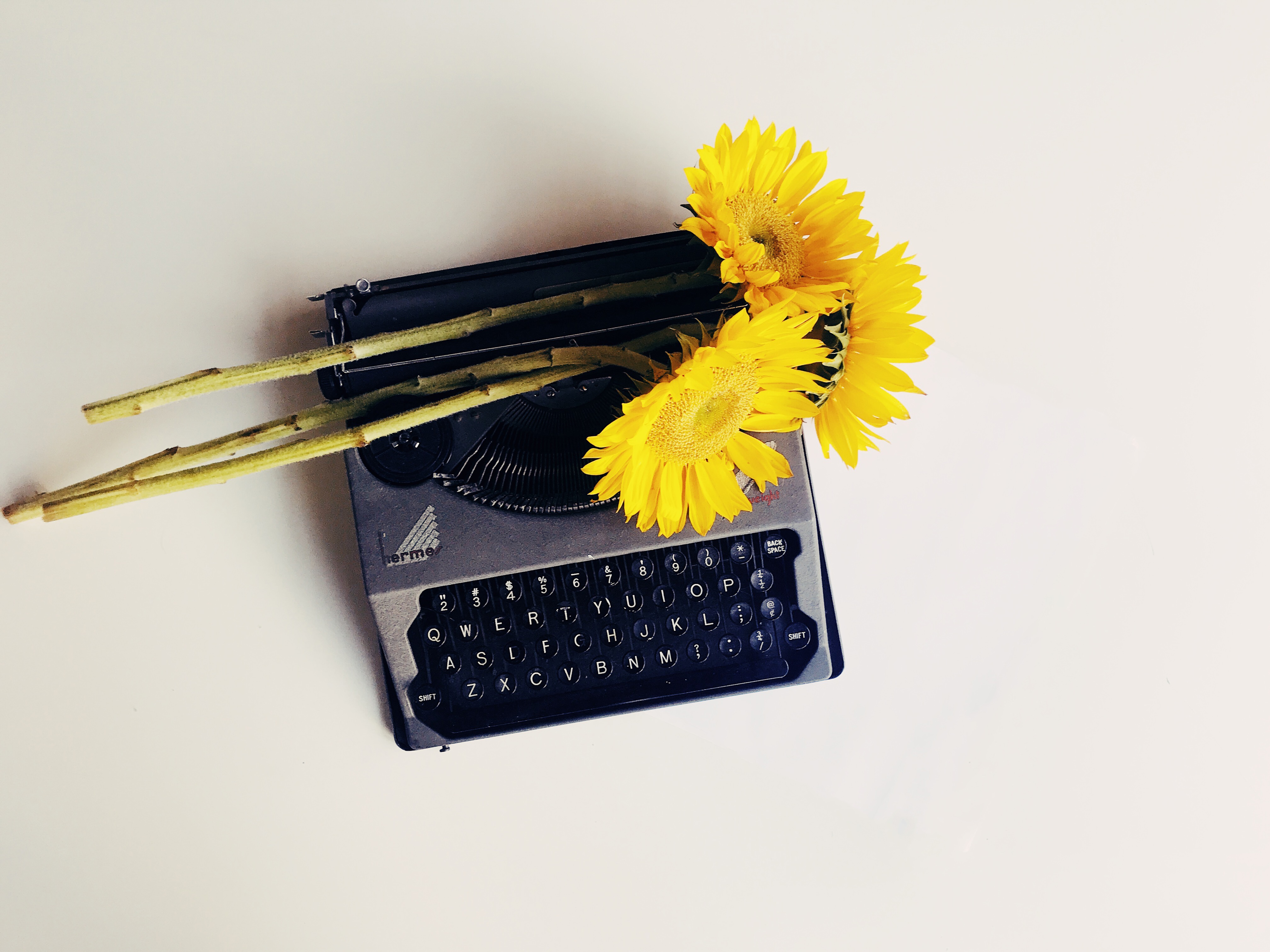 A charcoal grey Hermes typewriter with 3 sunflowers lying on top of it on a light background.