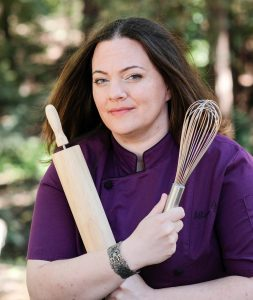 Baker in purple chef coat with rolling pin and whisk