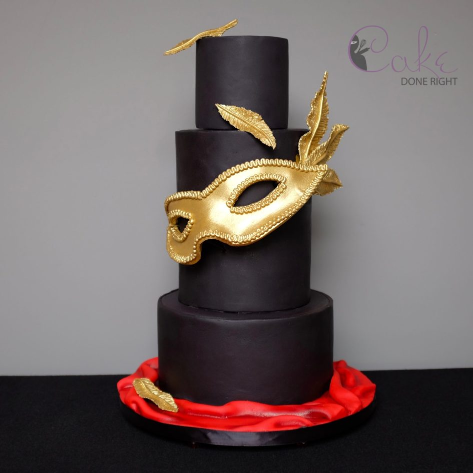 Black and gold masquerade cake with mask and feathers.