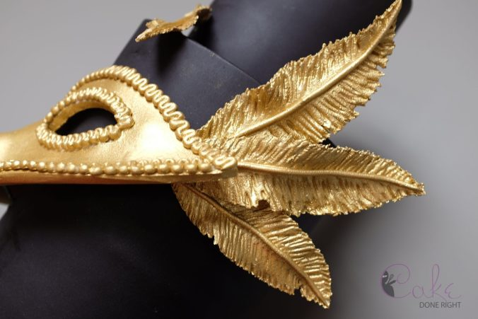 gold and black tiered masquerade cake feathers