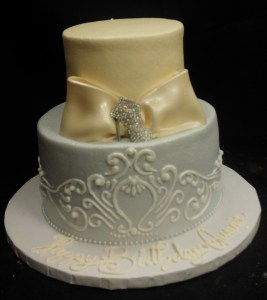 White cake with champagne colored ribbon detail