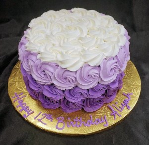 Purple and white cake with buttercream flowers all over