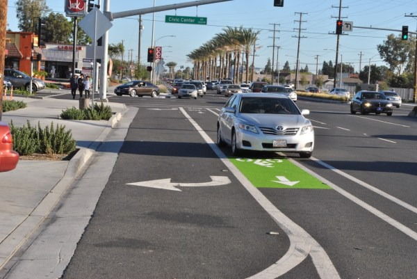 An automobile driving over the northbound Bristol Street bike lane where a newly painted green strip was placed late last month. A line of cars leading into the adjacent In-N-Out Burger is a common sight at this location.