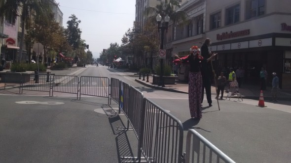 Stilt performers on Fourth Street. The barriers from the 5k that happened earlier in the day completely taken down until 11 a.m., an hour after the start of the open street event. Photo by Kristopher Fortin.