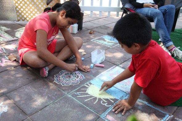 Sonia, 11, Brian 8, draw on the floor at Santa Ana resident's parklet in downtown Garden Grove. Photo by Kris Fortin