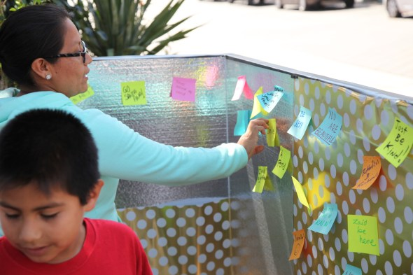 Margarita Solis, 39, adds a wish to the wishing wall at North Orange County's (Park)ing Day event. Photo by Kristopher Fortin
