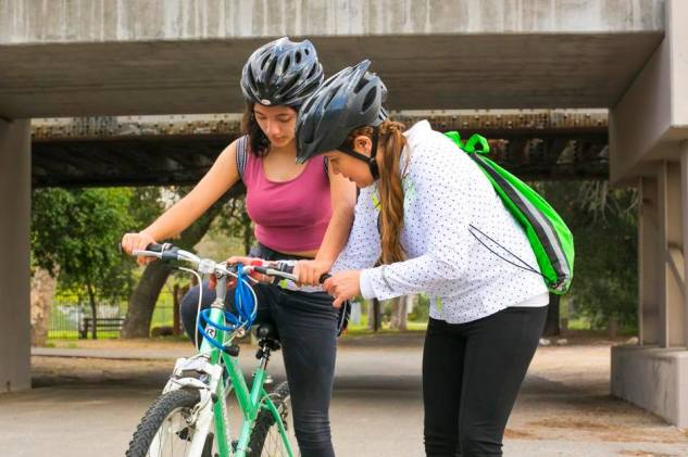 "SAAS member Rosario ""Charis"" Perez, left, helps Mary Leopo with her bike during a SAASy Mujeres ride."