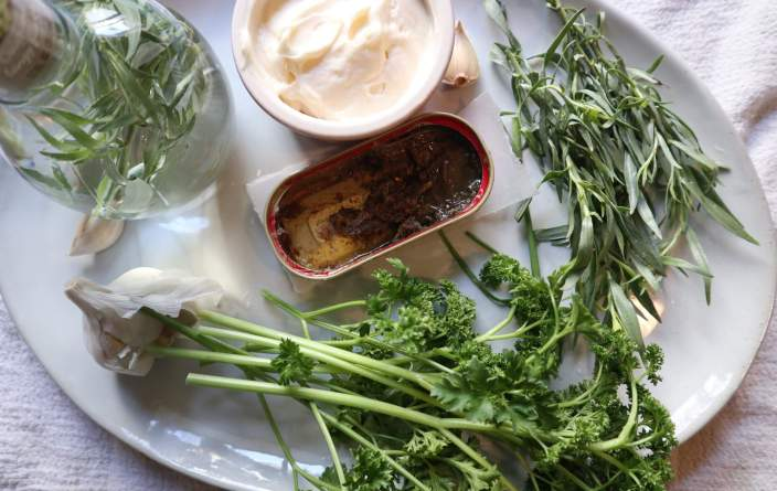 a plate with fresh herbs, mayonnaise, tarragon vinegar and anchovies, ingredients fora green goddess dressing recipe