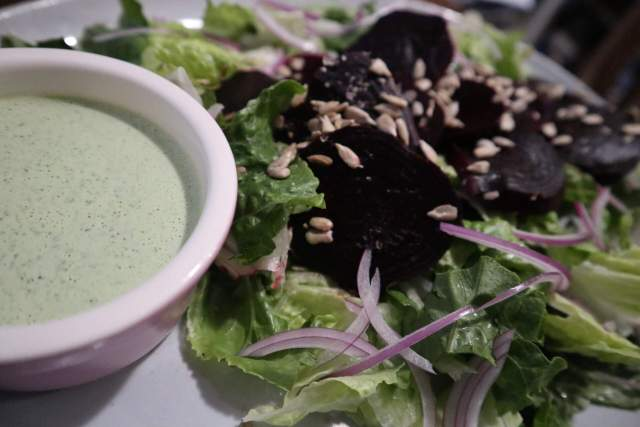 close up of a side dish holding green goddess dressing on a platter of salad with romaine and beets