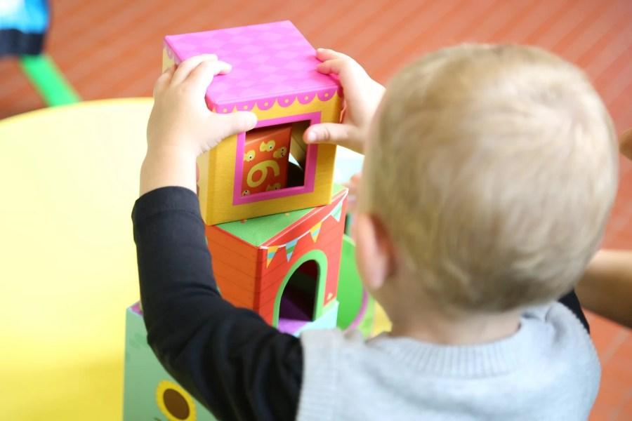 Bébé jouant avec des cubes empilables à la crèche