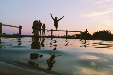 Une famille joue près de la piscine avec le soleil couchant