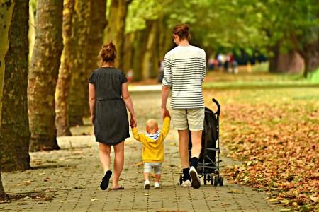 Parents baladant leur enfant avec une poussette