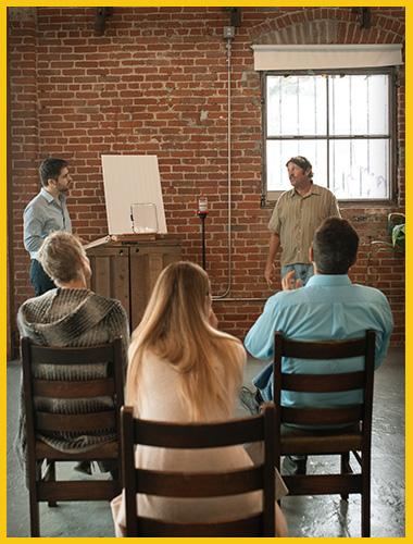 Un homme parle devant une assemblée, pendant qu'un professeur l'observe depuis un pupitre.