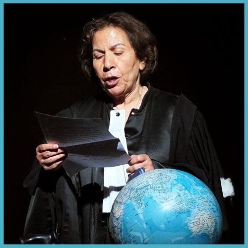 Une comédienne, costumée en juge, lit un texte devant un globe terrestre.