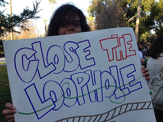 "Student Holding a poster that reads""Close the Loophole"""