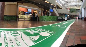 Foto del interior de un pasillo en el cual se muestra una alfrombra verde simbolizando el mes de la recreación