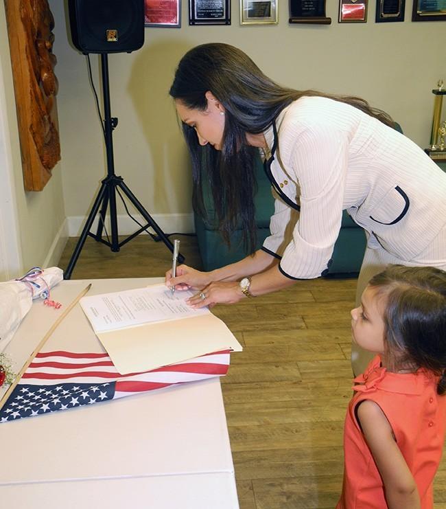 judge rivera correra signing - Cristina Rivera Correa of Kiwanis of Little Havana Appointed as a Judge