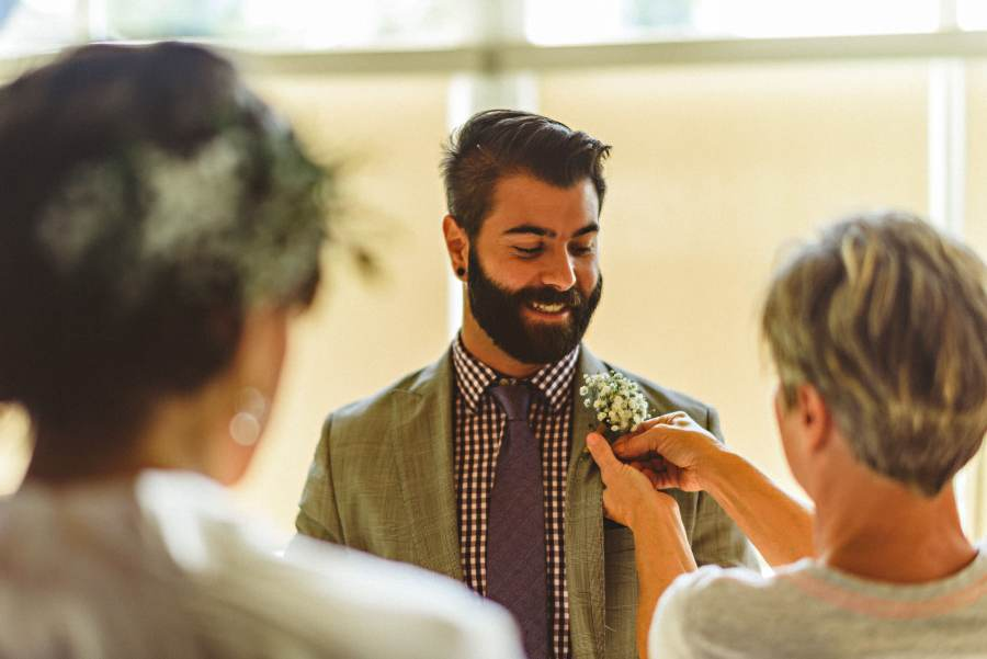 brother of bride having boutonniere put on