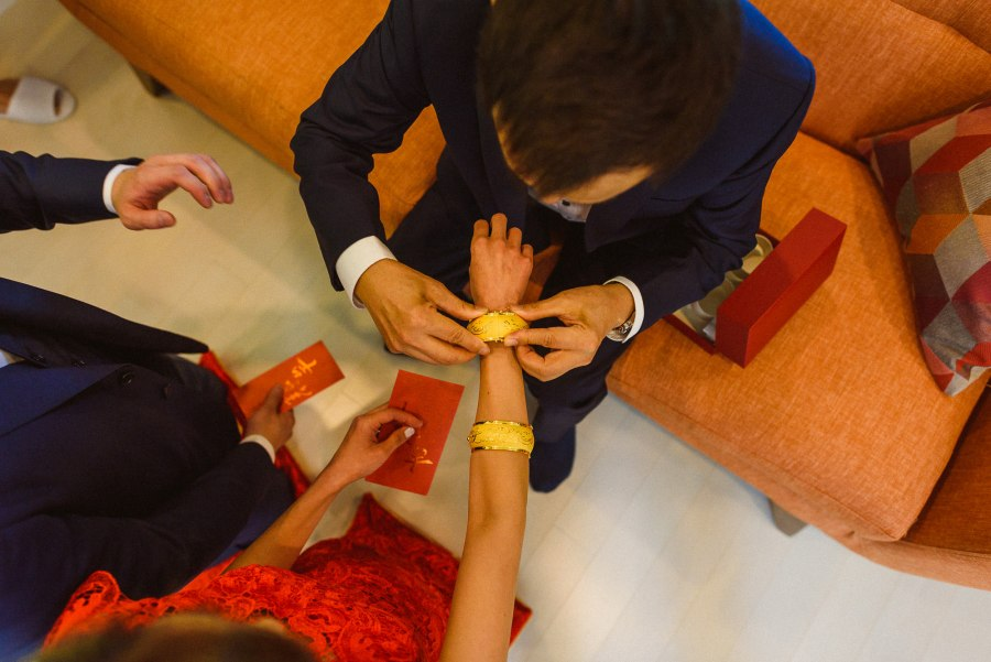 dad placing bracelet chinese tea ceremony wedding