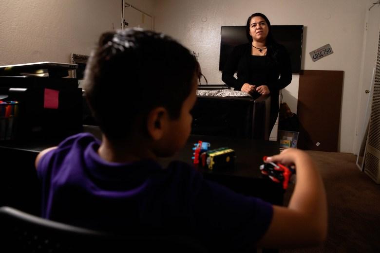 Alma Jiménez, a la derecha, se para en su sala de estar mientras su hijo Abraham, de 7 años, a la izquierda, juega en una mesa en su casa en Concord, California, el miércoles 30 de septiembre de 2020. Foto: Randy Vazquez / Bay Area News Group