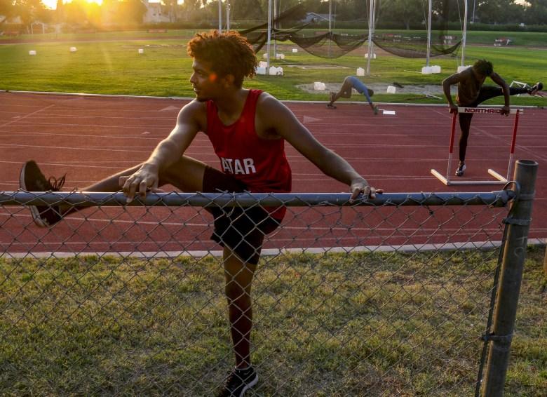 Ahmed Mohamed, a la izquierda, un estudiante atleta internacional de Qatar, se estira durante un entrenamiento de pista en la Universidad Estatal de California en Northridge junto a sus compañeros de equipo Yanla Ndjip-Nyemeck, en el centro, de Bélgica y Emmanuel Ihemeje, a la derecha, de Italia el 20 de octubre de 2020. El equipo no pudo entrenar con los entrenadores debido a las restricciones de COVID-19, pero un pequeño grupo de atletas se reunió durante la pandemia para hacer entrenamientos socialmente distantes un par de días a la semana. Foto de Logan Bik para CalMatters