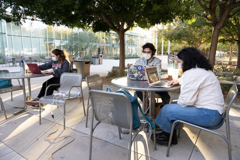 """La estudiante de psicología Merna Massoud, a la izquierda, se mantiene a distancia mientras estudia fuera del edificio de artes escénicas en Cal State Northridge con sus amigas Vem y Nairi Nazarian, una estudiante de química y biología, respectivamente, que son hermanos el 10 de noviembre de 2020. """"It & #039 Es difícil estudiar en casa y es agradable salir en un entorno menos poblado del campus y usar la conexión wifi para trabajar """". Dijo Massoud. Foto de Shae Hammon para CalMatters"""