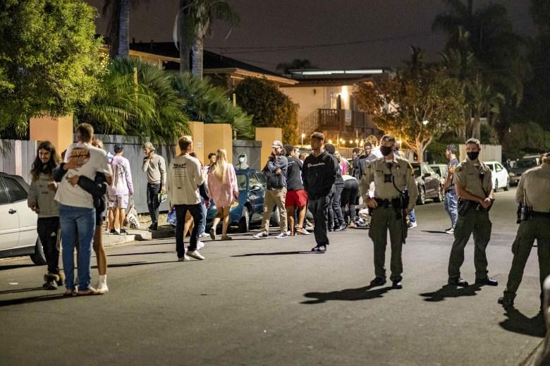 Los estudiantes sin máscara salen de una fiesta en una casa en Isla Vista el 29 de agosto de 2020, poco después de que la Oficina del Sheriff del Condado de Santa Bárbara y #039; s la cerrara por violar las pautas de salud pública del condado. El comienzo del trimestre de otoño en UC Santa Bárbara vio el regreso de las fiestas en casa a pesar de las pautas locales y del campus contra las reuniones. Foto de Max Abrams