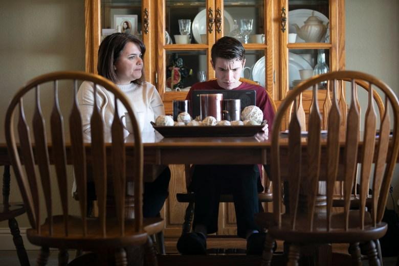 Linda Soares, a la izquierda, ayuda a su hijo, Daniel, de 16 años, con su tarea de historia en la mesa del comedor. Soares dice que ha podido aprender de la ayuda escolar de su hijo, que es un amigo, sobre la mejor manera de ayudarlo con su trabajo de clase. Foto de Anne Wernikoff para CalMatters