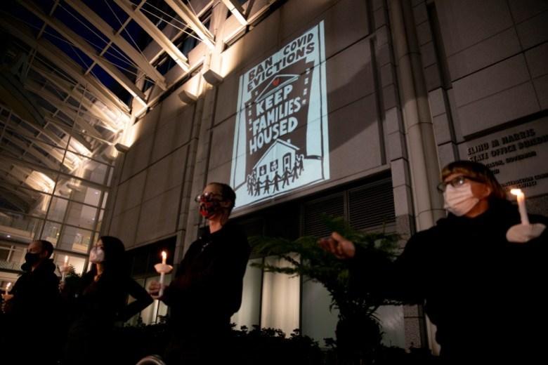 Activistas de vivienda y huelguistas de alquiler participan en una vigilia por los inquilinos que, según dicen, no estarán cubiertos por el plan de alivio de alquiler del gobernador Gavin Newsom en el edificio de oficinas de Elihu M. Harris, estado de California en Oakland el 29 de enero de 2021. Foto de Anne Wernikoff, CalMatters