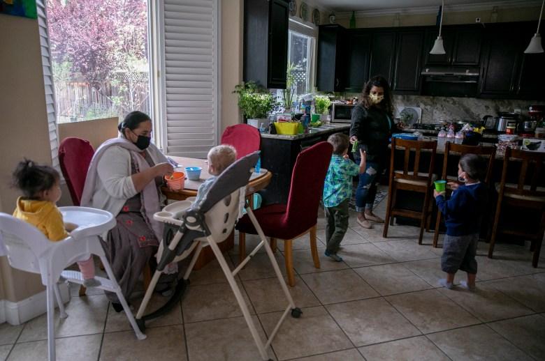 La asistente de la guardería Karamajit Kaur, izquierda, y Shruti Agarwal alimentan el desayuno de los niños en la guardería familiar Shruti en Livermore el 13 de abril de 2021. Foto de Anne Wernikoff, CalMatters