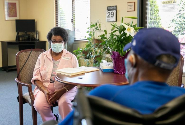 """Ouida Dill le sonríe a su esposo durante 60 años, David Dill, residente de Lincoln Glen Skilled Nursing Facility durante su primera visita al interior desde el inicio de la pandemia el 29 de marzo de 2021 en San José. Ouida ha sido vacunada, pero su esposo, que sobrevivió al COVID-19 a principios de este año, no puede vacunarse durante varias semanas más, por lo que deben permanecer a seis pies de distancia durante su visita. """"No puedo esperar a poder tocarlo"""", dijo Ouida. Foto de Anne Wernikoff, CalMatters"""