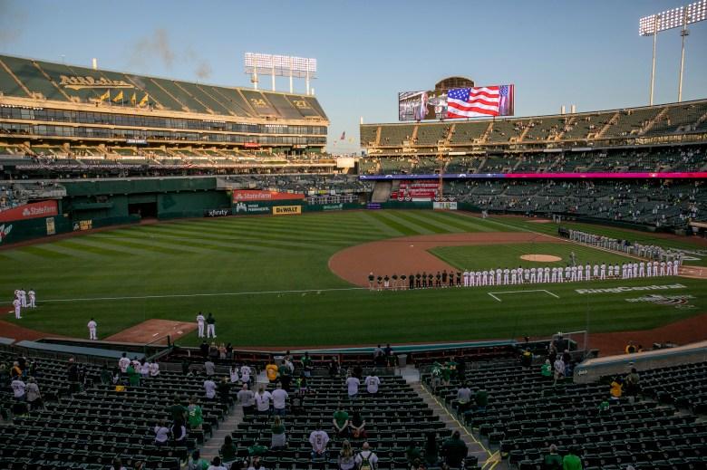 Jugadores y espectadores escuchan el himno nacional al comienzo del juego entre los Atléticos de Oakland y los Astros de Houston. Oakland Coliseum operó a una capacidad de 26% para permitir un amplio espacio entre los grupos. Foto de Anne Wernikoff, CalMatters