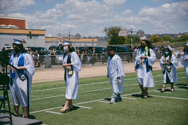 Los graduados hacen fila para recibir sus diplomas durante una ceremonia de graduación en Madison Park Academy en Oakland el 21 de mayo de 2021. Foto de Marissa Leshnov para CalMatters