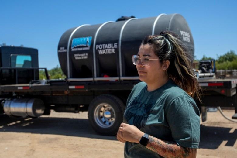 Luzvianey González observa cómo le entregan agua a su casa en Madera. el 10 de junio de 2021. Su familia ha estado comprando botellas de agua y duchándose en la casa de su hermana desde mayo, cuando su pozo se secó. Foto de Shae Hammond para CalMatters