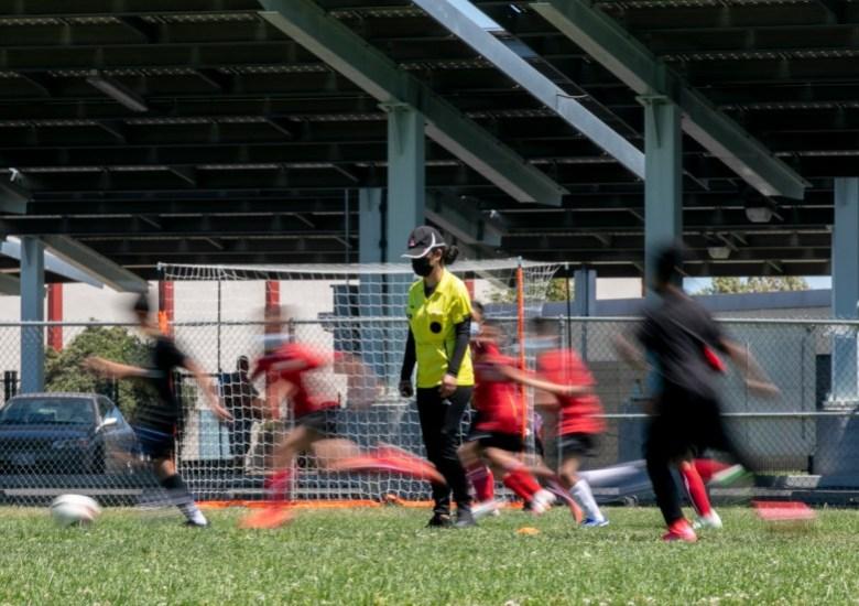 Los jugadores pasan corriendo junto a Claudeth mientras ella arbitra un partido de fútbol para una liga infantil local. Foto de Anne Wernikoff, CalMatters