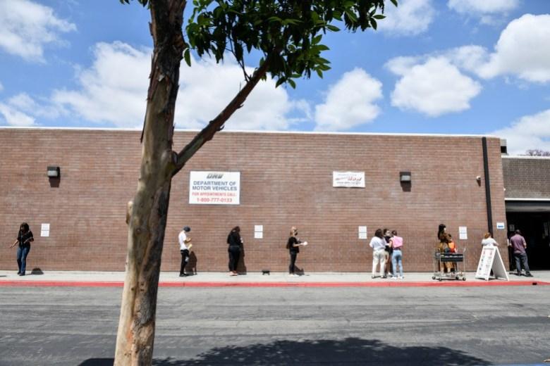 La gente espera en fila afuera de la oficina del Departamento de Vehículos Motorizados del estado en Bellflower, el 8 de junio de 2021. Pablo Unzueta para CalMatters