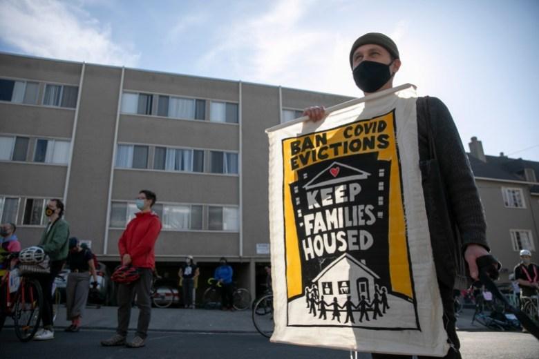 Andrew Rosenburg, residente de Oakland, sostiene una pancarta mientras protesta por los desalojos de alquileres durante la pandemia el 5 de diciembre de 2020 en Oakland. Foto de Anne Wernikoff, CalMatters
