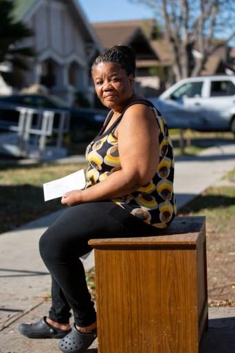 Deborah Bell-Holt se sienta frente a su casa en Jefferson Park, cerca del centro de Los Ángeles, el 21 de enero de 2021, sosteniendo su factura de agua y luz. Foto de Shae Hammond para CalMatters