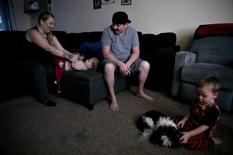 """Miranda Griswold viste a Jax, de 23 meses, para acostarse con su prometido, Matt Calhoun, mientras que Rhys, de tres años, juega con el perro de la familia en su casa de Merced el 8 de julio de 2021. """"¿Qué le estamos haciendo a nuestras familias?"""" preguntó Griswold sobre la política actual de licencia familiar. """"No hay apoyo"""". Foto de Anne Wernikoff, CalMatters"""