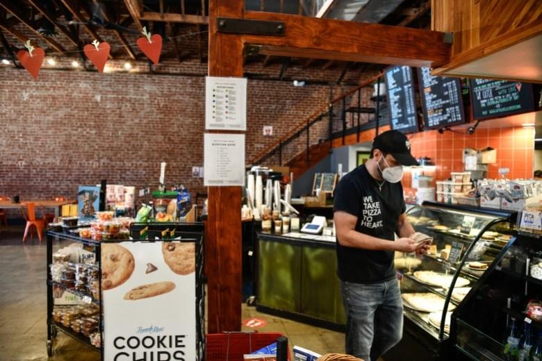 Andrew McDowell, propietario de una pequeña empresa de With Love Market & Cafe, reorganiza la pastelería en Los Ángeles, el 4 de agosto de 2021. Según McDowell, ha sido una tarea difícil mantener su negocio en pleno funcionamiento debido a la pandemia y falta de asistencia financiera del gobierno. Foto de Pablo Unzueta para CalMatters