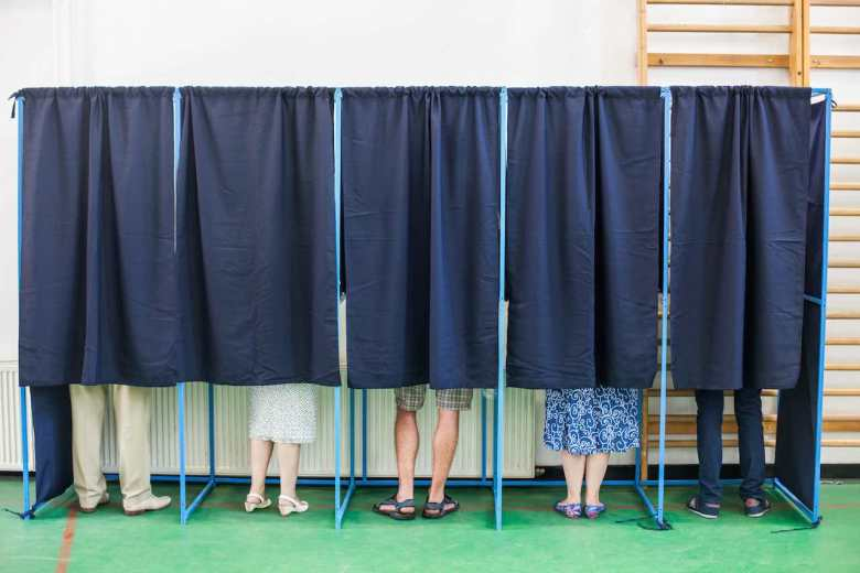 Color image of some people voting in some polling booths at a voting station.